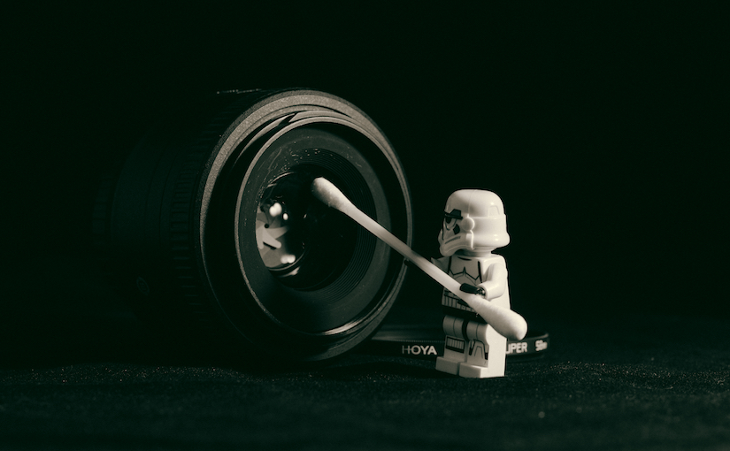 Lego stormtrooper cleaning a camera lens with a que tip.
