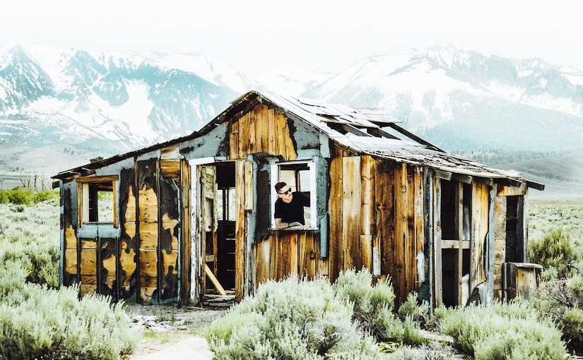 Man visible through window, standing in a falling apart shed that's in a field with mountains in the background.