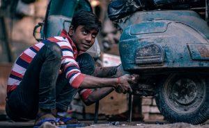 Man repairing motor bike.