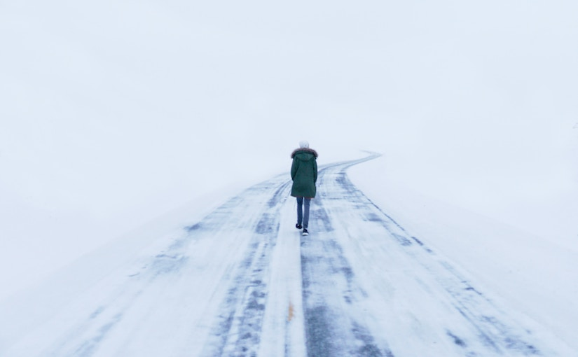Woman walking away from the camera down a snow covered road into a white abyss of snow.
