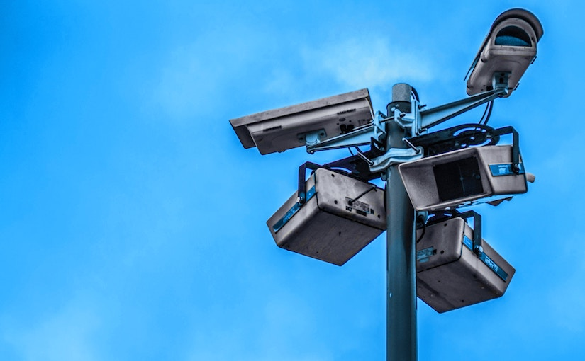Many security cameras on a light pole with a blue sky background.