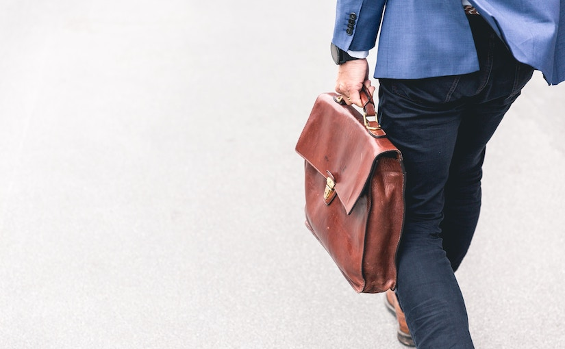 Man walking with work clothes and brief case in hand.