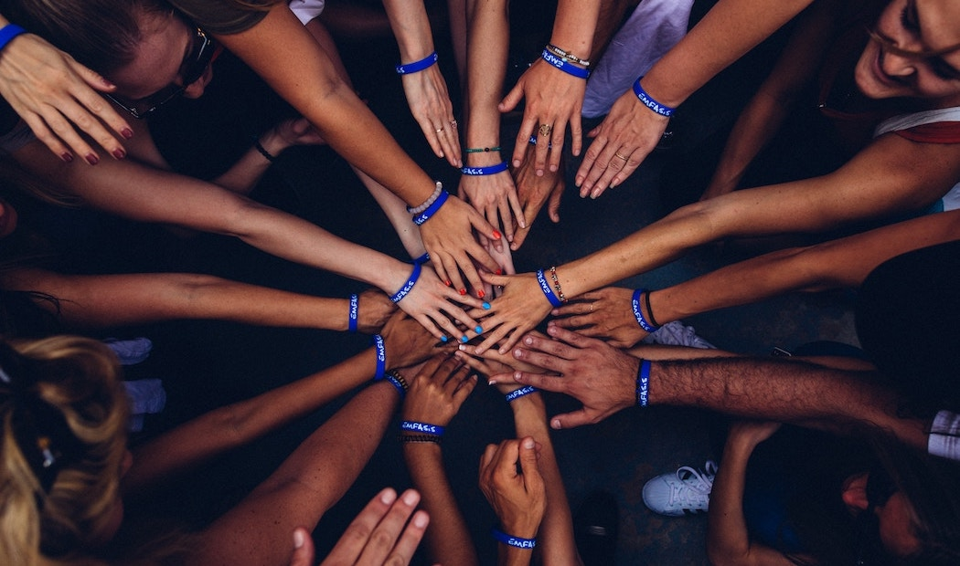 People's hands in a circle. All have a blue support bracelet.